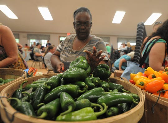 TaTanisha Davis looks through a basket of peppers at St. James Episcopal Church in Black Mountain, where Bounty & Soul holds one of its five weekly markets. Davis first came to the market in February of 2018 in an effort to reach her weight-loss goal and improve her quality of life.