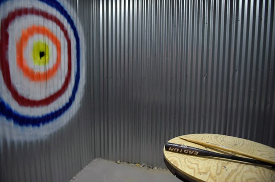"""A spray painted target, a baseball bat, and axe handle sit in a smash room, Friday, Aug. 9, 2019. Attendees choose their """"weapon"""" and music."""