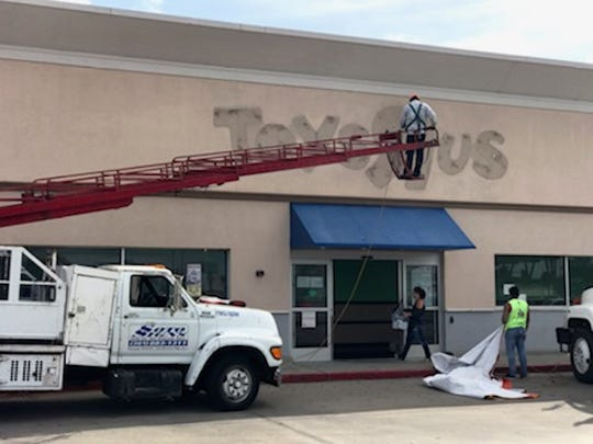 Workers remove the Toys R Us sign at 1220 Airline Road to make way for Spirit of Halloween, which is expected to open by the end of the month. Deanna Schulte, a manager for the seasonal Halloween costume store, carries supplies into the new location at  Promenade Shopping Center.
