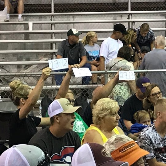 Bidders hold up cards representing their companies at the Junior fair swine show on Aug. 8 2019 at the Ross County Fair.