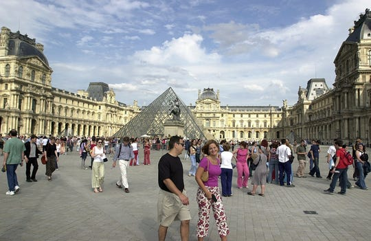 People stroll in the yard of the Louvre Museum in Paris, Sunday June 23, 2002.