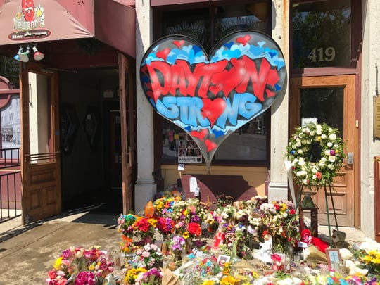 Aug. 9, 2019 E. Fifth Street: A memorial of flowers, cards, dolls and a Dayton Strong heart surround Ned Peppers outside the Aug. 4 mass shooting scene.