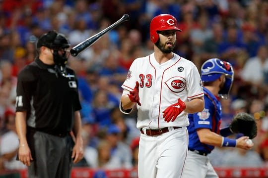 Cincinnati Reds left fielder Jesse Winker (33) tosses his bat aside after being walked in the third inning of the MLB National League game between the Cincinnati Reds and the Chicago Cubs at Great American Ball Park in downtown Cincinnati on Thursday, Aug. 8, 2019. The game was tied after three innings.