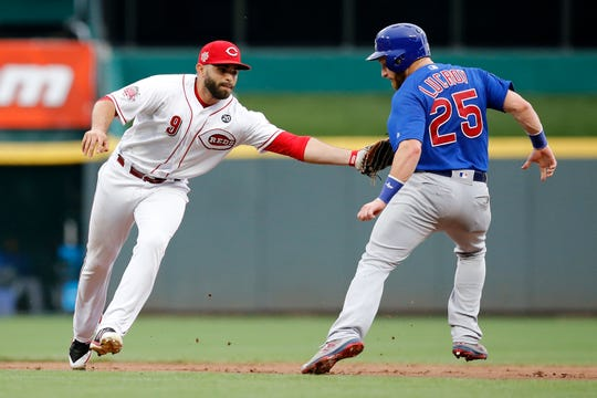 Cincinnati Reds second baseman Jose Peraza (9) tags Chicago Cubs catcher Jonathan Lucroy (25) as he runs for second in the second inning of the MLB National League game between the Cincinnati Reds and the Chicago Cubs at Great American Ball Park in downtown Cincinnati on Thursday, Aug. 8, 2019. The game was tied after three innings.