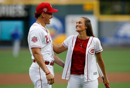 Cincinnati Reds second baseman Derek Dietrich cheers on his girlfriend, professional tennis player Monica Puig, after she serves the ceremonial first pitch before the first inning of the MLB National League game between the Cincinnati Reds and the Chicago Cubs at Great American Ball Park in downtown Cincinnati on Thursday, Aug. 8, 2019. The game was tied after three innings.
