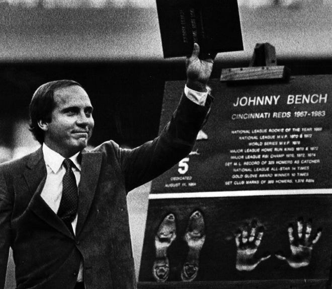 AUGUST 11, 1984: Former Cincinnati Reds catcher Johnny Bench waves a log of his major league home runs as he stands next to a plaque honoring him during ceremonies at Riverfront Stadium. Bench became the first Reds player to have his number retired. The plaque was placed at the stadium.