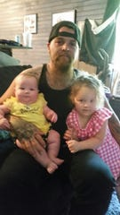 Eric Hardy cuddles his two daughters, Excee Hardy, 6 months, left, and Lillee Hardy, 4, right.