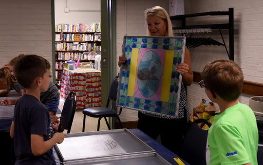 Youth services coordinator Cyndi Shutt shows She Smith (left), 8, and Isaiah Kaspar, 8, an example of a stained glass piece she made during Adventure 101's stained glass program at the Coshocton Public Library. The Adventure 101 program for youth was one of many new activities and events added to the library system over the past decade.