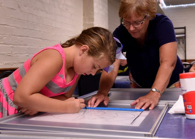 Madelyn Kliier, 8, traces a stencil on to glass with help from her grandmother, Carol Owens, during the recent Adventure 101 stained glass program, at the Coshocton Public Library. Young participants learned about the history of stained glass before trying it on recycled light covers from the library.