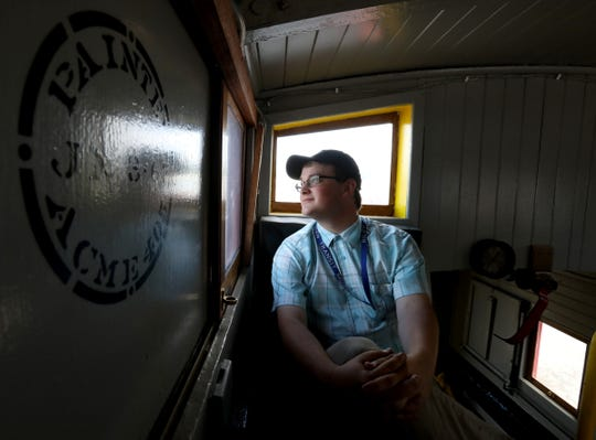 Riley Allendorf, 19 of Mt. Clemens and on the board of directors of the Michigan Transit Museum sits in the center cupola of a Detroit Toledo and Ironton DT&I caboose on Friday, August, 9, 2019. 