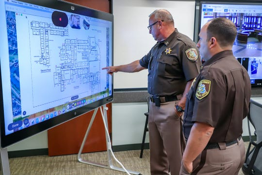Captain David Kennedy and Lt. Jason Arbo, of Macomb County Sheriff's office, look over the floor plan for L'Anse Creuse High School participating in a full-scale, active assailant training exercise at the Macomb County Emergency Management and Communications center in Mt. Clemens, Mich. on Thursday, Aug. 8, 2019. It was announced in October that the county's Office of Emergency Management and Communications had received a $316,860 federal School Violence Prevention Program grant.