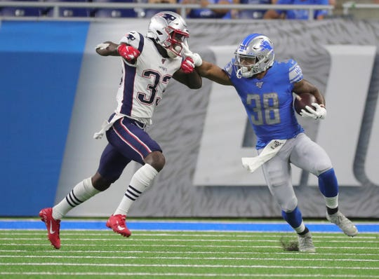 Lions running back Ty Johnson is tackled by Patriots defensive back Joejuan Williams during the second half of the Lions' 31-3 preseason loss to the Patriots on Thursday, Aug. 8, 2019, at Ford Field.