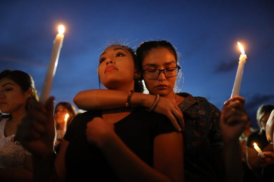 People attend a candlelight vigil at a makeshift memorial honoring victims of a mass shooting which left at least 22 people dead, on August 7, 2019 in El Paso, Texas.