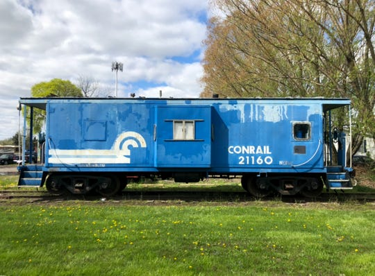 Before it's restoration, a Conrail bay window caboose numbered 21160 sits on the tracks owned by the Michigan Transit Museum before it was restored. 