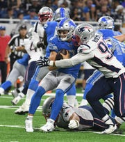 Lions quarterback David Fales is sacked by Patriots' Derek Rivers in the second quarter.