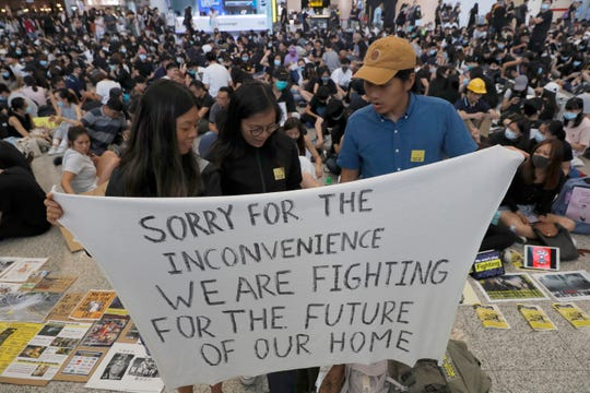 Protesters hold up a banner during a demonstration at the airport in Hong Kong Friday, Aug. 9, 2019. Pro-democracy activists rallied at the airport Friday even as the city sought to reassure visitors of their welcome despite the increasing levels of violence surrounding the 2-month-old protest movement.