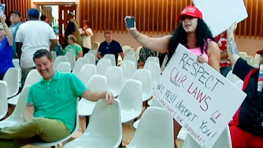 """This photo from video provided by KVOA-TV shows Alex Kack, in the green shirt at left, laughing at a protester during a vote to put a """"sanctuary city"""" initiative on the November ballot during a meeting of the Tucson, Ariz., City Council Tuesday, Aug. 6. Kack is mystified that video of him simply laughing at the meeting has captivated the internet. Kack, also known as """"#GreenShirtGuy,"""" told The Associated Press on Thursday that social media reaction spawned by a news clip of him shaking with laughter at a Tucson City Council meeting has been """"surreal."""""""
