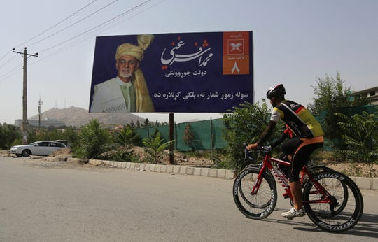 Afghan men rides cycle past an election hoarding of a presidential candidate Ashraf Ghani in Kabul, Afghanistan Friday, Aug. 9, 2019.