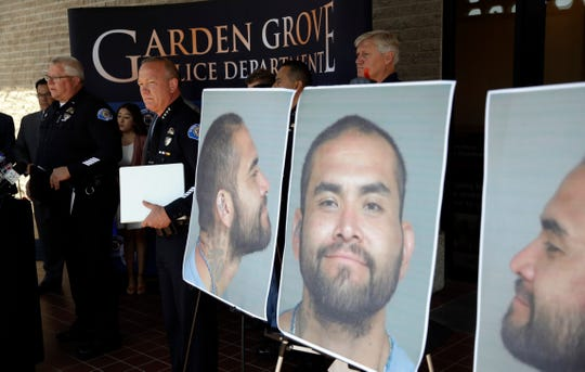 Garden Grove Police Chief Tom DaRe, center, and PIO Carl Whitney address the media next to a booking mug shot of Zachary Castaneda posted outside of the Garden Grove Police Department headquarters in Garden Grove, Calif.