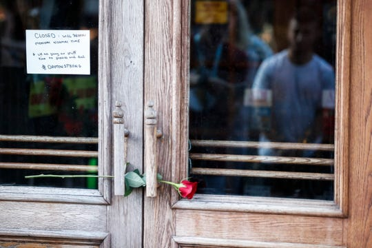 Mourners place flowers at the front of Ned Peppers bar as they gather at the scene of a mass shooting before a prayer vigil, in Dayton, Ohio.