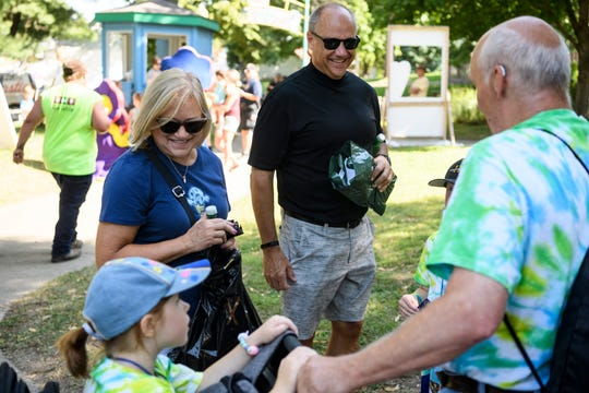 Janel Marcovis, top left, and Steve Scarpino, top right, talk to fairgoers after handing the children envelopes filled with $5 to honor their dead father Ed Scarpino during the second day of the Iowa State Fair in Des Moines, Iowa, Friday, Aug. 9, 2019. They spent several hours passing out 400 Eddie's High $5 envelopes.