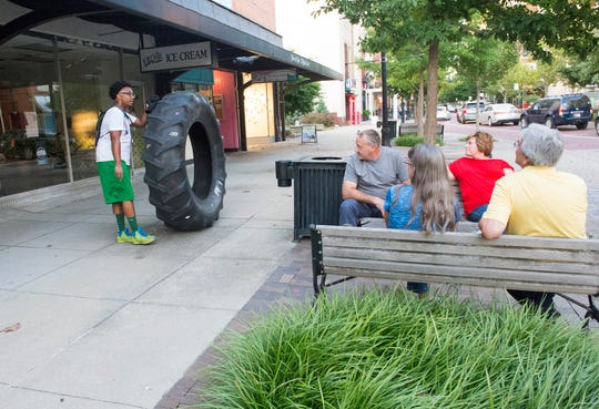 """DeAndre Wilson, 27, tops to chat with a group of people while rolling a 230-pound tire around Evansville, Ind. that reads """"cancer sucks"""" with the goal of raising awareness about cancer in the community Wednesday afternoon, Aug. 7, 2019. Wilson inherited the tire five years ago from his father who rolled it around the last 18 months of his life as he battled stage four liver and colon cancer."""