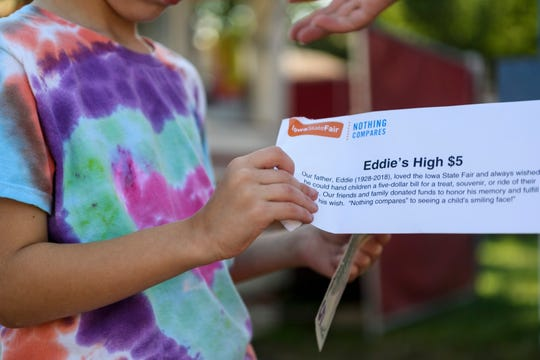 Jack Waite opens his Eddie's High $5 envelope given to him at random by Steve Scarpino and Janel Marcovis, not pictured, during the second day of the Iowa State Fair at the fairgrounds in Des Moines, Iowa, Friday, Aug. 9, 2019. Marcovis and Scarpino passed out 400 envelopes to honor the memory of their father Ed Scarpino, who died in Sept. 2018.