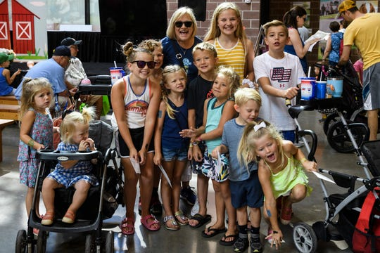 Janel Marcovis, top center left, poses for a picture with a large family of fairgoers after handing all of the children envelopes filled with $5 to honor her dead father Ed Scarpino during the second day of the Iowa State Fair at Iowa State Fairgrounds in Des Moines, Iowa, Friday, Aug. 9, 2019. Scarpino, a photographer and State Fair volunteer, died in Sept. 2018 at the age of 90.