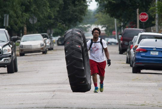 """DeAndre Wilson, 27, rolls a 230-pound tire around Evansville, Ind. that reads """"cancer sucks"""" with the goal of raising awareness about cancer in the community Wednesday afternoon, Aug. 7, 2019. Wilson inherited the tire five years ago from his father who rolled it around the last 18 months of his life as he battled stage four liver and colon cancer."""