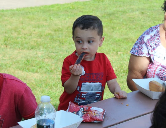 """Angelo Black, 3, of Gibsonburg, chows down on a hot dog during """"Cookout with the Cops"""" at Williams Park Friday."""