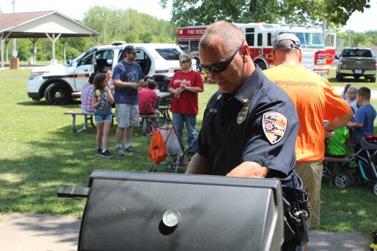 """Gibsonburg Police Chief Dan Collins works a grill full of hot dogs during """"Cookout with the Cops"""" at Williams Park."""