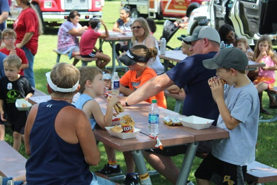 Families chow down on a picnic-style cookout with Gibsonburg first responders and village officials.