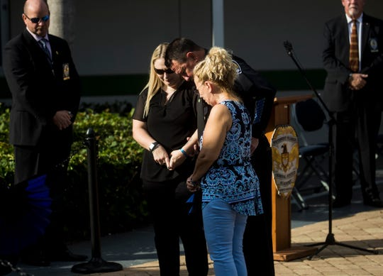 Sanibel Island police chief, William Dalton escorts Debra Neri and Allison Schulze during a Fallen Officer memorial ceremony honoring Anthony Neri at the Southwest Florida Public Service Academy in Fort Myers on Friday August, 8, 2019. Neri died of natural causes during a training drill in May of this year. Neri is is Anthony's widow and Allison is his daughter.