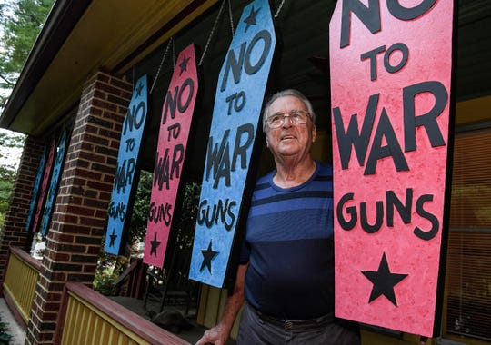 "John Acorn of Pendleton stands on his porch with 12 panels of artwork with words ""No To War Guns"" Friday."