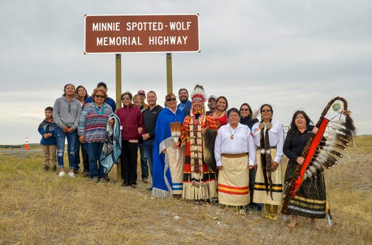 Family of Minnie Spotted-Wolf pose with dignitaries under the Minnie Spotted-Wolf Memorial Highway sign during the dedication ceremony along US Highway 89 on the Blackfeet Indian Reservation, August 9, 2019.  Minnie Spotted-Wolf, a member of the Blackfeet Tribe, was the first Native American woman to serve in the United States Marine Corps from 1943-1947, serving in World War II as a heavy equipment operator.