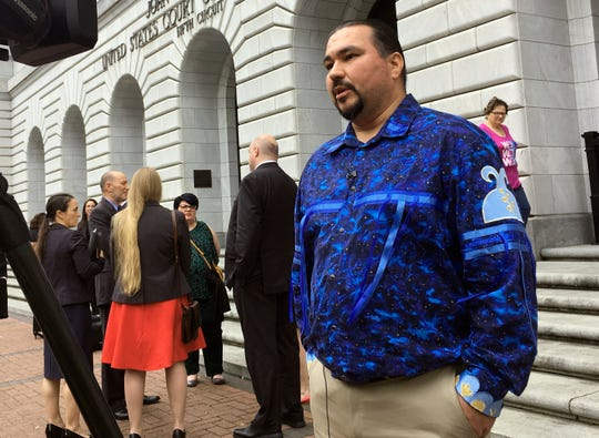 FILE - In this Wednesday, March 13, 2019, file photo, Tehassi Hill, tribal chairman of the Oneida Nation, stands outside a federal appeals court in New Orleans, following arguments on the constitutionality of a 1978 law giving Native American families preference in adoption of Native American children. On Friday, Aug. 9, 2019, the 5th U.S. Circuit Court of Appeals in New Orleans upheld the constitutionality of the law. (AP Photo/Kevin McGill, File)