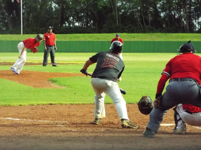 In this file photo from January 2017, AutoSpot Canyons Coby Barnes lays down a sacrifice bunt during the  Canyons' 5-3 win over the Blue Jays  in the Amateur Summer Wood Bat League at LeoPalace Guam Resort.