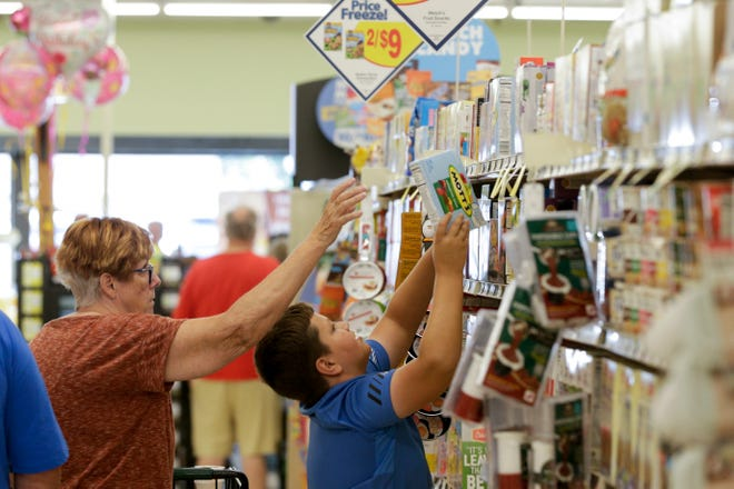 Charlotte Rayburn helps her grandson, Keaton Simmons, 10, with an item during the grand opening of Needler's Fresh Market, 2250 Teal road, Friday, Aug. 9, 2019 in Lafayette.