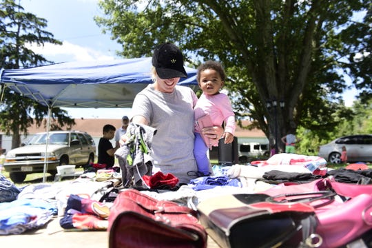 Lenzie Gray and her one-year-old daughter, Niayeli, both of Bucyrus, look through items at a Crestline yard sale during the annual Lincoln Highway Buy-Way sale.