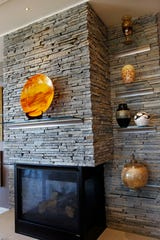 The fireplace was moved and then clad in stacked stone. Floating glass shelves were also added to display artwork.