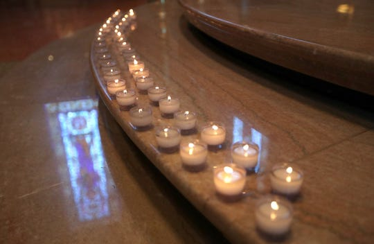 Forty-two candles, one for each fatal shooting victim in the recent mass shootings in Gilroy, California, El Paso, Texas, and Dayton, Ohio, are lit on the altar during a midday prayer service at the Cathedral of St. John the Evangelist on North Jackson Street in Milwaukee on Friday.