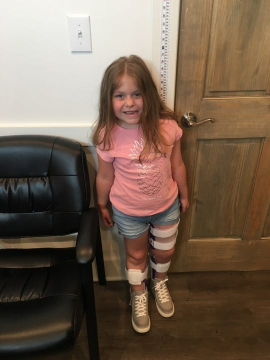 Annadelle proudly stands for the first time, unassisted, since a rare illness paralyzed the 6-year-old in 2018.