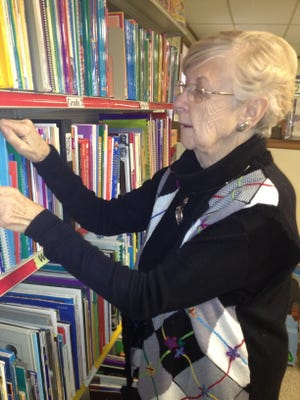 Marilyn Carey is shown in a photo from 2013 organizing books at the Back to School Teachers Store.