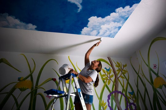 Molly Wooley paints the ceiling, Friday, Aug. 9, 2019, at Valerie's House for Children in Naples.