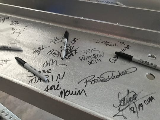 Signatures on a steel beam at a topping-off ceremony for the first phase of Moorings Park Grande Lake on Aug. 9, 2019.