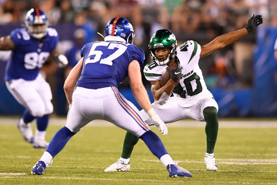 New York Jets running back Trenton Cannon, right, rushes against New York Giants linebacker Ryan Connelly (57). The Jets face the Giants in the first preseason game at MetLife Stadium on Thursday, August 8, 2019, in East Rutherford.