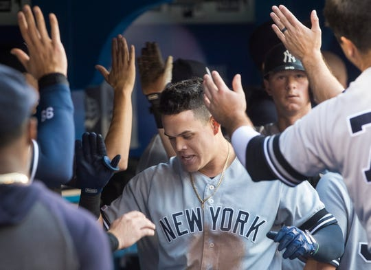 New York Yankees' Gio Urshela celebrates with teammates after hitting his second two-run home run of the night, against the Toronto Blue Jays during the third inning of a baseball game Thursday, Aug. 8, 2019, in Toronto.