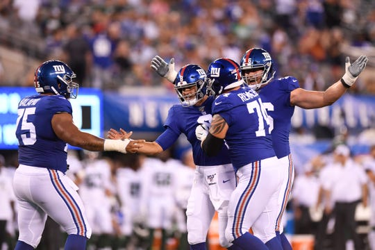 The New York Giants offensive line celebrates rookie quarterback Daniel Jones' (8) touchdown in his NFL debut against the New York Jets. The Jets face the Giants in the first preseason game at MetLife Stadium on Thursday, August 8, 2019, in East Rutherford.