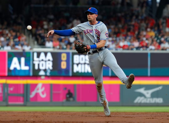 Second baseman Jeff McNeil #6 of the New York Mets makes a play on a ground out hit by Ronald Acuna Jr. #13 of the Atlanta Braves in the first inning at SunTrust Park on June 19, 2019 in Atlanta, Georgia.