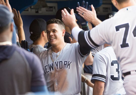 New York Yankees third baseman Gio Urshela (29) celebrates in the dugout after hitting a two run home run during the third inning against the Toronto Blue at Rogers Centre.